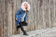 Attractive hipster girl in warm jacket near wooden fence. Outdoors Stock Photos