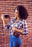 Attractive hipster holding camera and looking at it Stock Photography