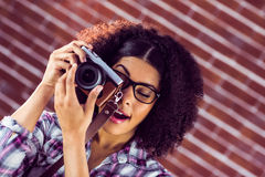 Attractive hipster photographing with camera Stock Photography