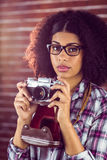 Attractive hipster photographing with camera Royalty Free Stock Photos