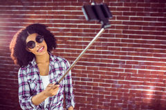 Attractive hipster taking selfies with selfiestick Royalty Free Stock Photo