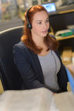 Attractive hipster woman with headset in office stock photography