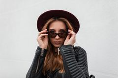 Attractive hipster young woman with sexy lips with beautiful lips in vintage sunglasses in trendy black leather jacket posing