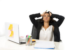 Attractive hispanic businesswoman or secretary suffering breakdown and headache in stress at office. Young attractive hispanic businesswoman or secretary Stock Photography