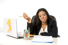 Attractive hispanic businesswoman or secretary suffering breakdown and headache in stress at office. Young attractive hispanic businesswoman or secretary Royalty Free Stock Images