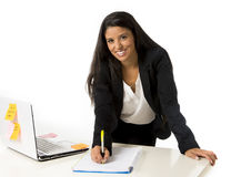 Attractive hispanic businesswoman or secretary taking notes standing leaning on office computer desk Royalty Free Stock Image
