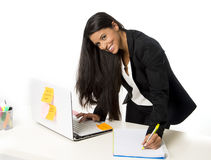 Attractive hispanic businesswoman or secretary taking notes standing leaning on office computer desk Royalty Free Stock Photos