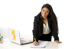 Attractive hispanic businesswoman or secretary taking notes standing leaning on office computer desk Stock Photos