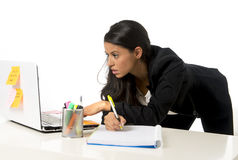 Attractive hispanic businesswoman or secretary taking notes standing leaning on office computer desk Stock Images