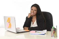 Attractive hispanic businesswoman sitting at office desk working on computer laptop smiling happy Stock Photos