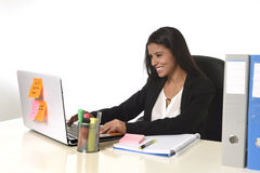 Attractive hispanic businesswoman sitting at office desk working on computer laptop smiling happy Royalty Free Stock Image