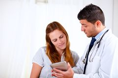Attractive hispanic doctor conversing with a woman Royalty Free Stock Photos