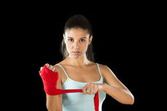 Attractive hispanic fitness woman doing self hand wraps before boxing or fighting workout. Young attractive hispanic fitness woman doing self hand wraps before stock image