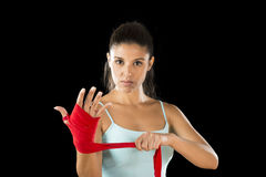 Attractive hispanic fitness woman doing self hand wraps before boxing or fighting workout. Young attractive hispanic fitness woman doing self hand wraps before stock photos