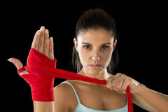 Attractive hispanic fitness woman doing self hand wraps before boxing or fighting workout. Young attractive hispanic fitness woman doing self hand wraps before stock images