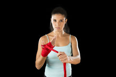 Attractive hispanic fitness woman doing self hand wraps before boxing or fighting workout. Young attractive hispanic fitness woman doing self hand wraps before stock photography