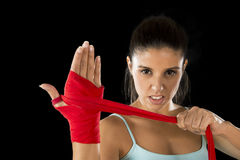 Attractive hispanic fitness woman doing self hand wraps before boxing or fighting workout. Young attractive hispanic fitness woman doing self hand wraps before royalty free stock image