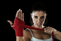 Attractive hispanic fitness woman doing self hand wraps before boxing or fighting workout. Young attractive hispanic fitness woman doing self hand wraps before royalty free stock photos