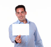 Attractive hispanic guy holding a white card Stock Photo