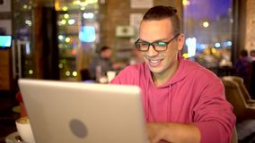 Attractive hispanic man with a beautiful smile using laptop in cafe. Technologies concept. man with glasses. Attractive hispanic man with a beautiful smile stock video footage