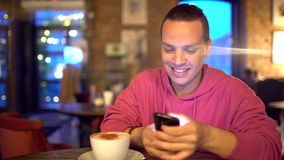 Attractive hispanic man a businessman, a student or a startup with an attractive smile using mobile phone. Handsome. Young man texting on smartphone in cafe. 4 stock video footage