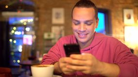 Attractive hispanic man a businessman, a student or a startup with an attractive smile using mobile phone. Man texting. On smartphone and drinking coffee in stock video footage