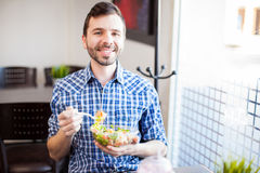 Attractive Hispanic man eating healthy food. Portrait of a young Hispanic man eating a salad at a restaurant and smiling Stock Photography