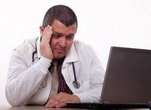 Attractive hispanic thirties male doctor headache Stock Photos