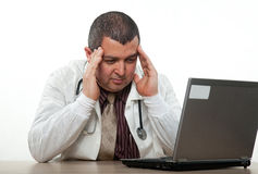 Attractive hispanic thirties male doctor headache Royalty Free Stock Images