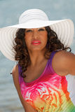 An attractive hispanic woman at the beach wearing a white hat Stock Photos
