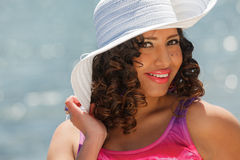 An attractive hispanic woman at the beach wearing a white hat Royalty Free Stock Photography