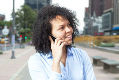 Attractive hispanic woman in the city at phone Royalty Free Stock Image