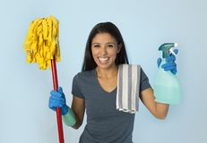 Attractive hispanic woman happy proud as home or hotel maid cleaning and housekeeping holding soap spray and mop royalty free stock photos