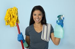 Attractive hispanic woman happy proud as home or hotel maid cleaning and housekeeping holding soap spray and mop. Young attractive hispanic woman happy proud as Stock Image