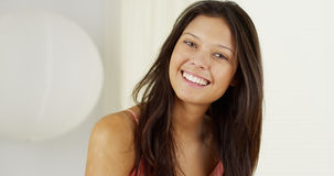 Attractive Hispanic woman playing with hair and smiling royalty free stock images