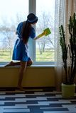 Attractive housemaid cleaning window. Stock Photo