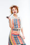 Attractive housewife with curlers in kitchen apron holding soup ladle Stock Photo