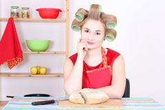 Attractive housewife cutting bread in the kitchen Royalty Free Stock Photos
