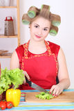 Attractive housewife cutting salad in the kitchen Stock Images