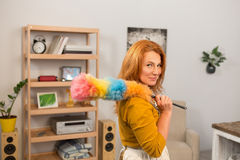 Attractive housewife holding whisk for dust on her shoulder. Mid aged female standing in the room finishing cleaning Royalty Free Stock Photo