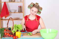 Attractive housewife with vegetables in the kitchen Stock Photo