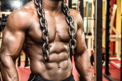 Attractive hunky black male bodybuilder posing with iron chains Stock Images