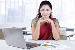 Attractive indian businesswoman smiling in office. Picture of beautiful indian entrepreneur wearing traditional clothes in the office with laptop and financial Royalty Free Stock Images