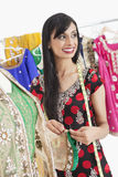 Attractive Indian female dressmaker looking away while working on an outfit Royalty Free Stock Photography