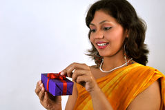 Attractive Indian woman opening a gift Stock Photo