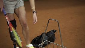 Attractive injured girl with a sports bag in her hands comes to the indoor tennis court to train. Making first ball. Serve. Slow motion stock video footage