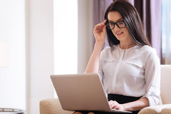 Attractive intelligent businesswoman fixing her glasses. Involved in work. Attractive nice intelligent businesswoman looking at the laptop screen and fixing her Stock Photo