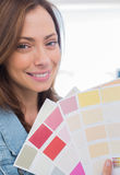 Attractive interior designer holding up colour samples Royalty Free Stock Photo