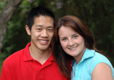 Attractive interracial couple. Young smiling couple; asian and caucasian in a park Stock Images