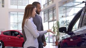 Couple chooses car at the dealership. Attractive interracial couple choosing car at the dealership. Pretty caucasian women pointing her hand on new vehicle Royalty Free Stock Photos